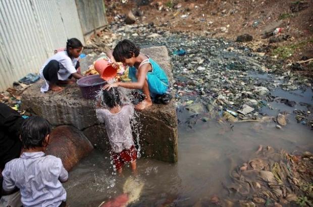 Retrato da falta de saneamento: crianças brincando em meio da água suja e lixo. Atual situação da saúde pública e saneamento básico no Brasil.